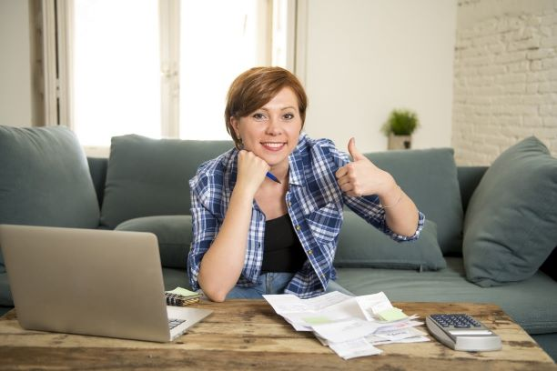 woman banking and accounting home monthly and credit card expenses with computer laptop doing paperwork smiling relaxed in financial success