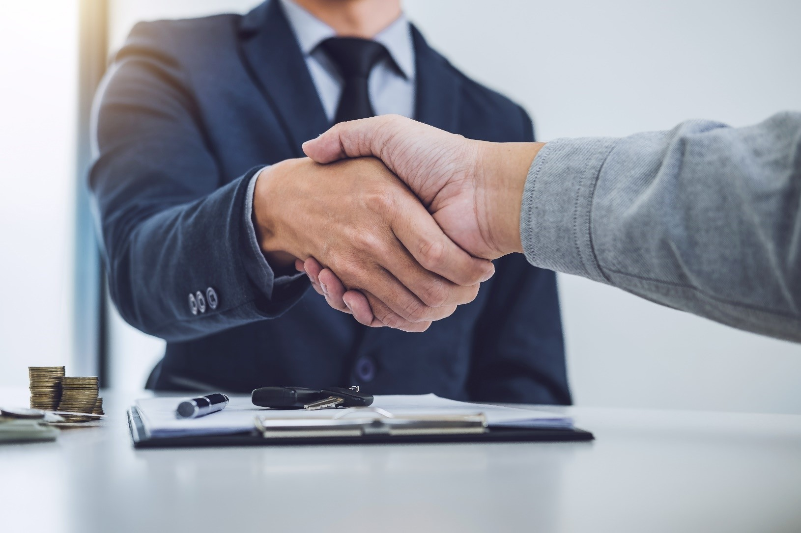 Borrower and lender shake hands after finalising a car loan