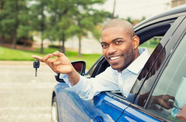 Man smiles holding keys to the new car he bought with a personal loan