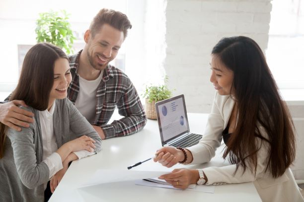 A young couple talking to a woman, approved for a loan thanks to their great credit rating