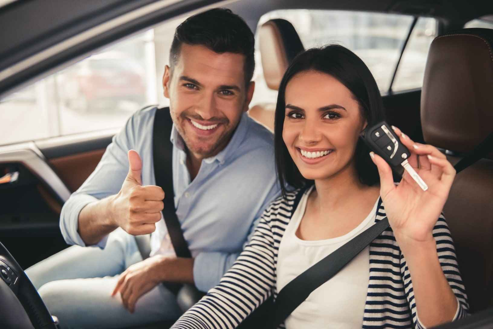 Couple holding a car key looking at camera and smiling while sitting in their new car