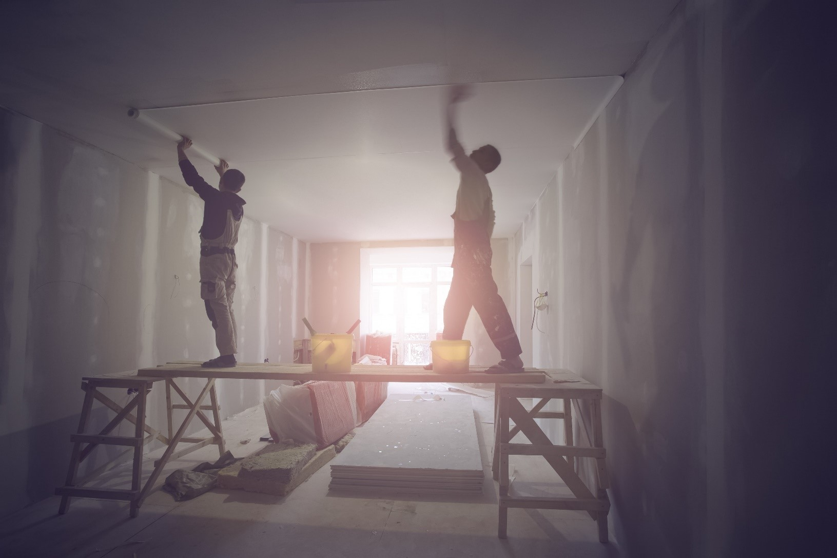 Two construction workers install a ceiling in a home renovation