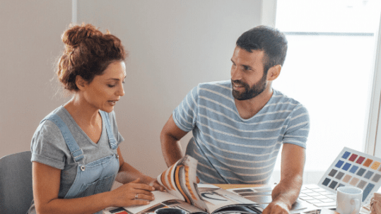 Couple planning a home renovation in front of a table