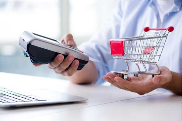 Man holding a cart and POS struggling to make payments for shopping purchases