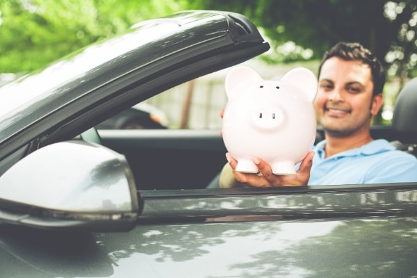 Man sitting in a car holding a piggy bank