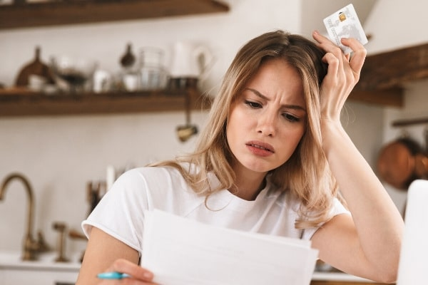 Stressed women holding a plastic credit card while looking at paper documents