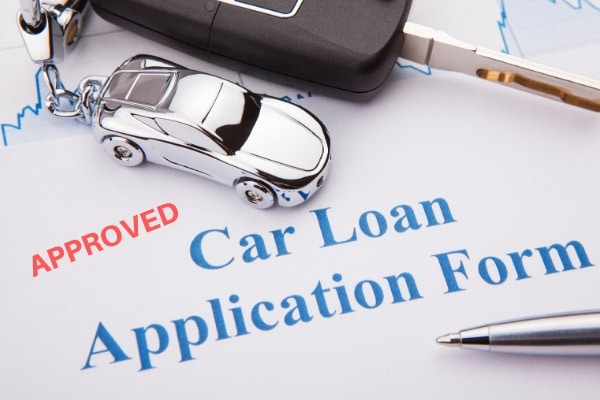a car loan application form with a pen and car key