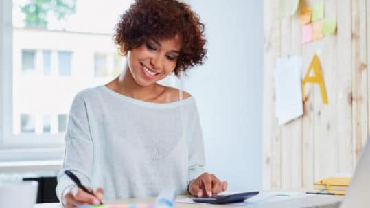 Happy woman working on a loan refinancing application with a calculator