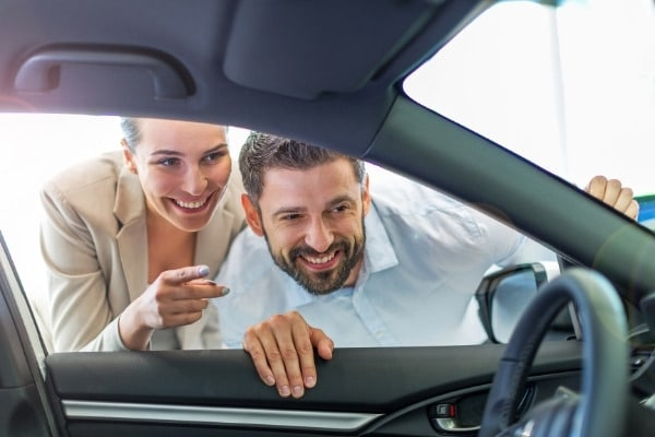 Young couple in the showroom choosing a car