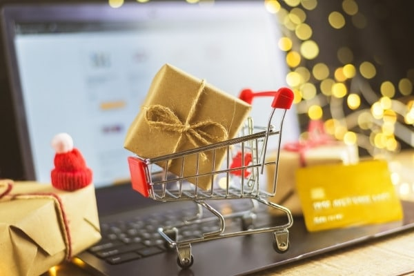 Trolley with Christmas gifts, bank card and laptop