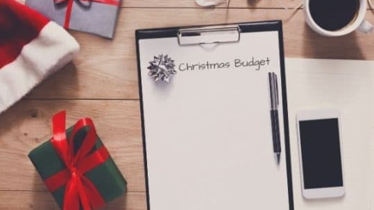 """Pen, wrapped gifts, Santa hat, phone and notebook with words """"Christmas budget"""""""