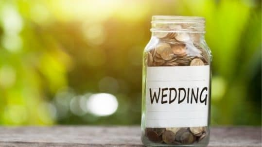 "Word ""wedding"" with coins in glass jar"