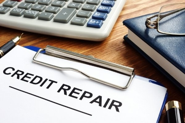 Credit repair form in a clipboard, pen and calculator