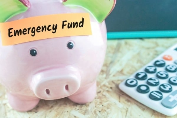 Calculator and word emergency fund on note paper on piggy bank