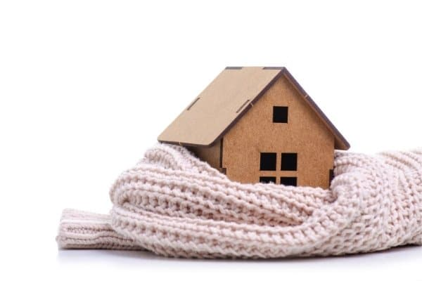 Toy wooden house wrapped in a warm scarf