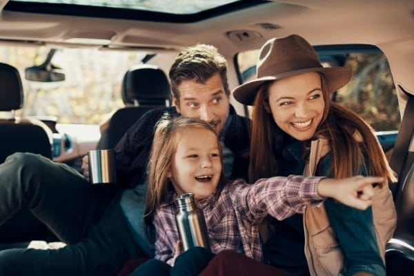 Excited family on a road trip in car