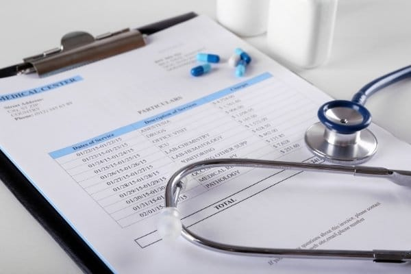 Medical bills with stethoscope on a desk
