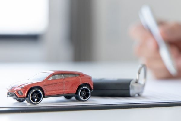 A person's hand signing car loan agreement contract with toy car on desk